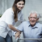 Nurse Helping Disabled Senior Man